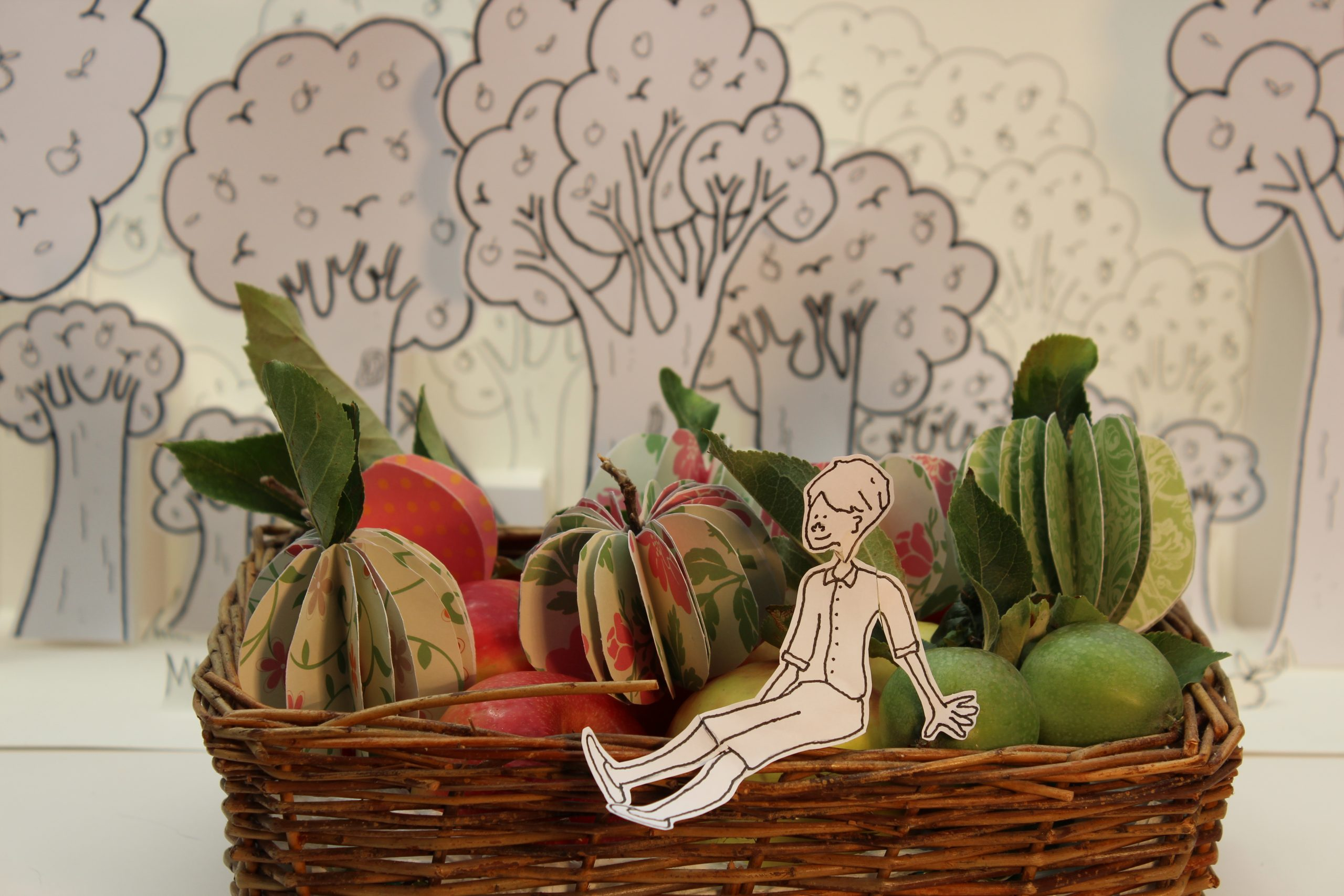 Photograph of a frame from stop-frame animation. A boy drawn in pen sits on the edge of a real basket filled with both real and paper apples. In the background stands a copse of pop-up pen drawn apple trees.