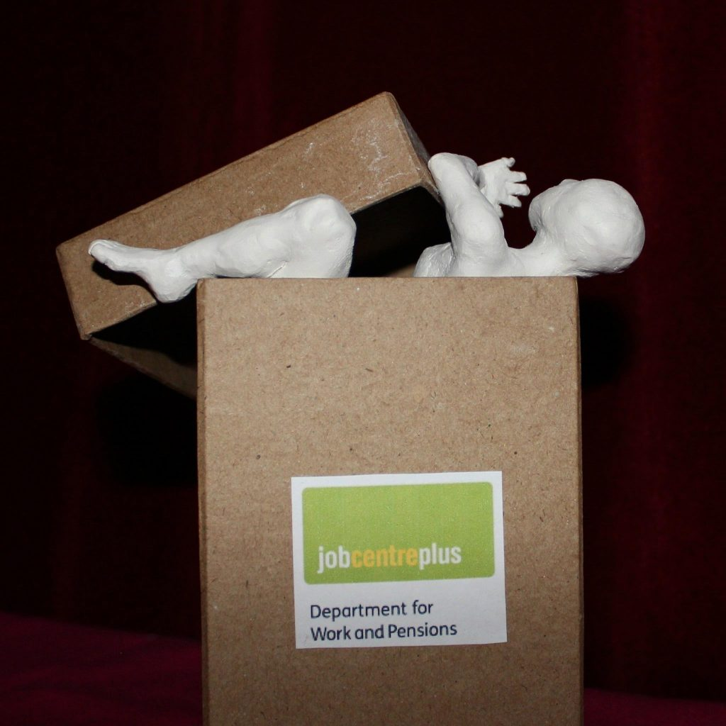 A small cardboard box labelled Job Centre Plus, Department for Work and Pensions. A white human figure sculpted from clay is pushing the lid of the box off. It's leg, arm and head protrude from the top of the box.