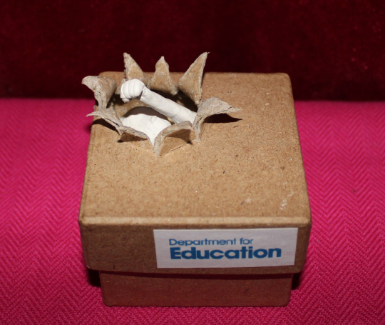A box labelled Dept of Education has a hole torn in the corner where a figurine's fist has punched through the lid. The arm and head of the figure is revealed within.