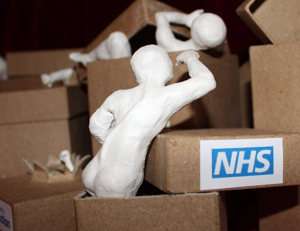 Clay figures emerge from boxes. In the foreground a figure with a curved spine eches out with an arm as he climbs from a box labelled NHS.