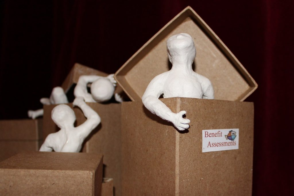 Clay figures reach and climb, emerging from boxes. In the foreground a figure stands looking up from within a box, the lid pushed away. The box is labelled Benefit Assessments and has a fish logo akin to that used by Atos who carry out the government's contracts to assess sick and disabled people for their fitness to work. Their chasing of targets for large bonuses have led to claimants dying in poverty or taking their own lives.