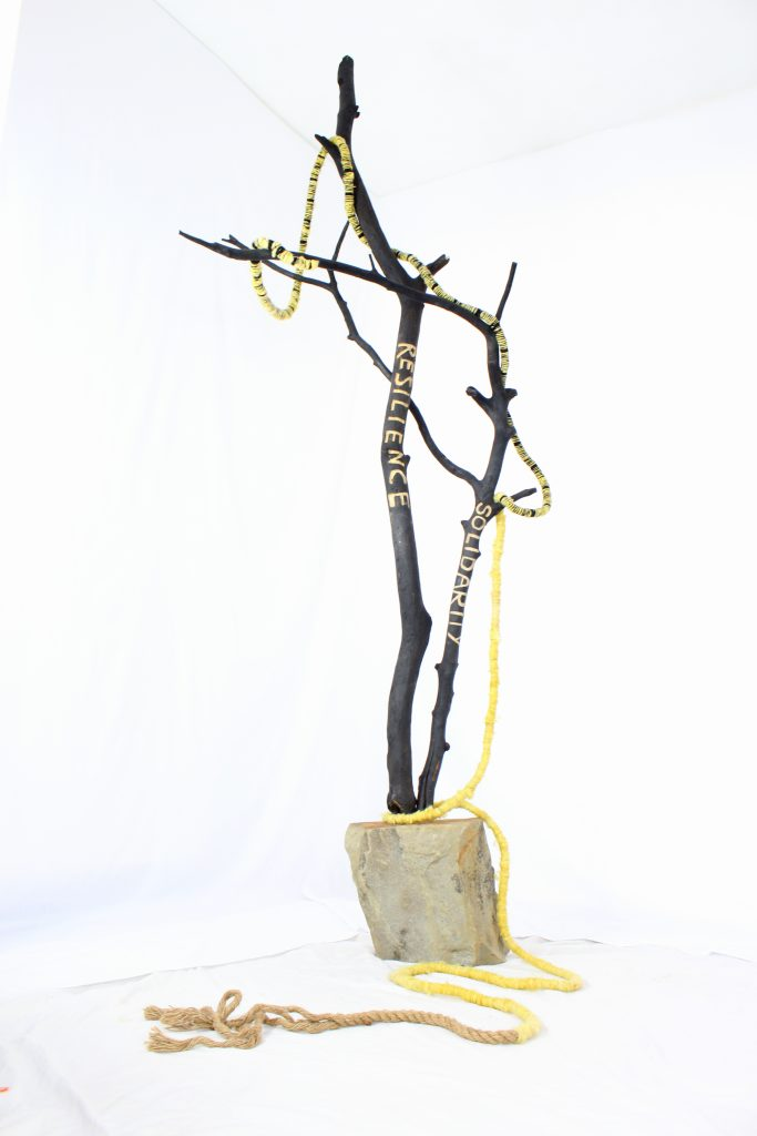 Two charred intertwining branches carved with the words Resilience and Solidarity stand emerging from a sandstone block. A rope of yellow and black sheeps wool winds around the branches