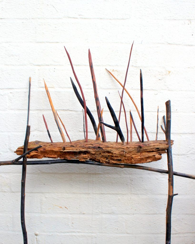 Dead wood rests precariously on willow branches. Pointed coloured lances rise from insect holes.