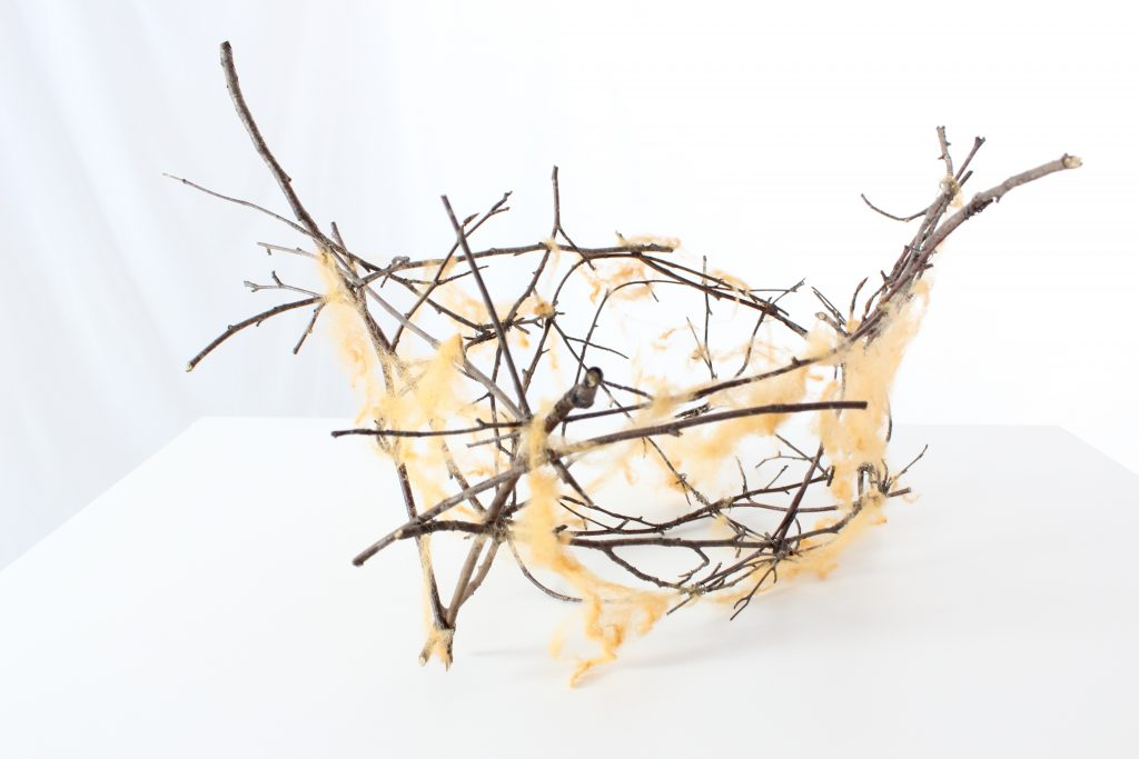 basket formed loosely of twigs and wisps of naturally dyed sheeps wool